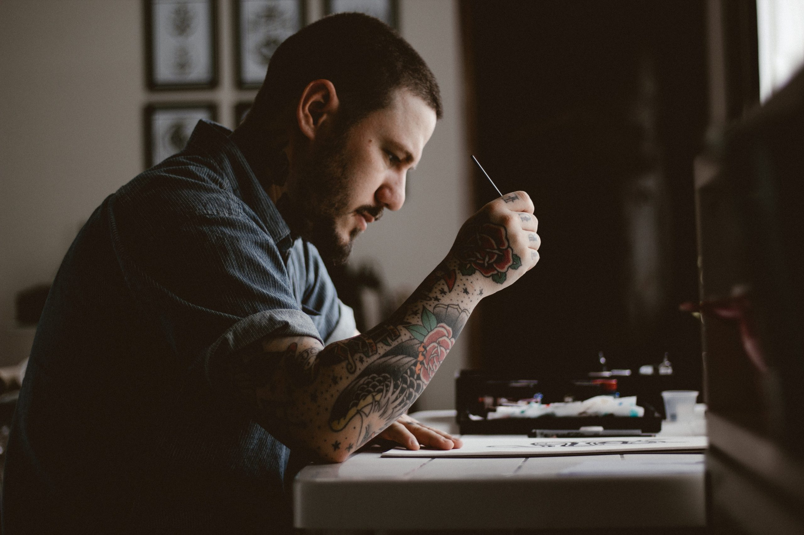 Artist sits at a drawing table